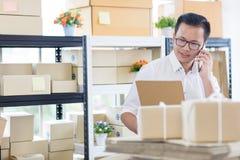 Homem de negócios asiático novo no uso ocasional da camisa que chama o smartphone, imagem de stock