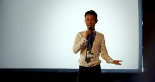 Homem de negócios asiático novo que fala no seminário do negócio no auditório 4k video estoque