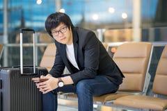 Homem de negócios asiático novo que senta-se no terminal de aeroporto Foto de Stock Royalty Free