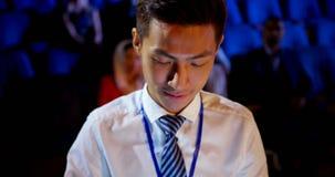 Homem de negócios asiático novo que usa a tabuleta digital durante o seminário do negócio no auditório 4k video estoque