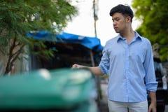 Homem de negócios asiático novo que verifica o lixo no outd das ruas fotografia de stock