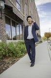 Homem de negócios asiático que anda ao falar no telefone celular fora imagens de stock royalty free