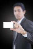 Homem de negócios asiático que empurra o cartão conhecido branco. fotografia de stock