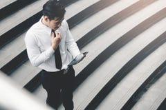 Homem de negócios asiático que está na escadaria exterior e que usa a tabuleta imagem de stock royalty free