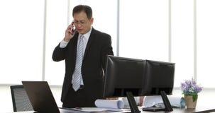 Homem de negócios asiático que fala ao telefone celular video estoque