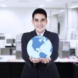 Homem de negócios asiático que guarda o globo Fotografia de Stock