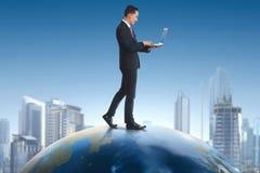 Homem de negócios asiático que guarda o portátil ao andar na terra imagem de stock royalty free
