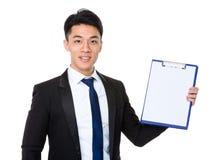 Homem de negócios asiático que mostra com a página vazia da prancheta imagem de stock