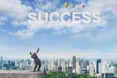 Homem de negócios asiático que puxa a palavra do sucesso no céu imagens de stock royalty free