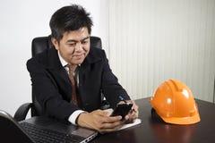 Homem de negócios asiático que trabalha e que guarda o telefone do smrt Imagens de Stock Royalty Free