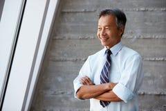Homem de negócios asiático Standing Against Wall no escritório moderno Fotos de Stock