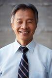 Homem de negócios asiático Standing Against Wall no escritório moderno Fotografia de Stock Royalty Free