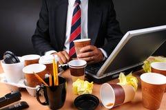 Homem de negócios assentado em sua mesa desarrumado Imagem de Stock