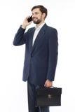 Homem de negócios atrativo com mala de viagem que fala no telefone imagem de stock royalty free