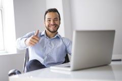 Homem de negócios atrativo mexicano em seu 30s que trabalha no escritório domiciliário moderno com portátil do computador fotografia de stock royalty free