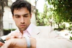 Homem de negócios que olha o relógio. Imagens de Stock