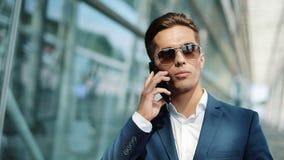 Homem de negócios atrativo que está a fala center do escritório próximo em um smartphone Estilo do negócio, viajante, uma comunic filme