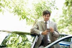Homem de negócios com carro e smartphone. fotos de stock