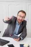 Homem de negócios atrativo que senta-se na mesa e que mostra o polegar acima imagens de stock
