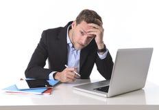 Homem de negócios atrativo que trabalha no esforço na dor de cabeça de sofrimento do computador da mesa de escritório Foto de Stock Royalty Free