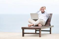 Homem de negócios autônomo na praia com portátil Fotos de Stock Royalty Free