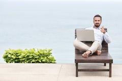Homem de negócios autônomo na praia com portátil Imagem de Stock