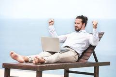 Homem de negócios autônomo na praia com portátil Fotografia de Stock