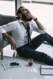 Homem de negócios bêbado que senta-se no assoalho foto de stock