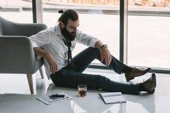 Homem de negócios bêbado que senta-se no assoalho imagens de stock royalty free