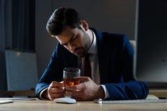 homem de negócios bebido cansado que olha o vidro do uísque fotografia de stock