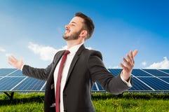 Homem de negócios bem sucedido com os braços extendidos no photovo solarpower foto de stock royalty free