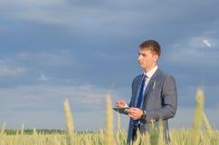 Homem de negócios bem sucedido do fazendeiro no campo com portátil Imagem de Stock