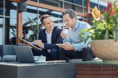 Homem de negócios bem sucedido esperto que come o café Imagens de Stock Royalty Free