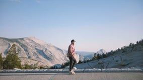 Homem de negócios bem sucedido feliz novo da vista lateral que anda ao longo da opinião épico do cenário da montanha no parque na filme