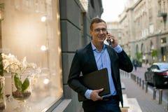 Homem de negócios bem sucedido no terno com o portátil na cidade imagem de stock royalty free