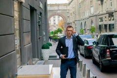 Homem de negócios bem sucedido no terno com o portátil na cidade foto de stock royalty free