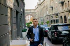 Homem de negócios bem sucedido no terno com o portátil na cidade fotografia de stock