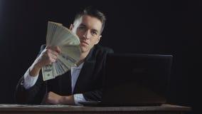 Homem de negócios bem sucedido novo com as notas de dólar empilhadas em um fã que trabalha em um portátil filme