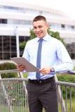Homem de negócios bem sucedido novo com tabuleta fora imagem de stock royalty free