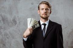 Homem de negócios bem sucedido novo no terno que guarda o dinheiro sobre o fundo cinzento fotografia de stock royalty free