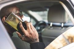 Homem de negócios bem sucedido novo que fala no telefone que senta-se no assento traseiro de um carro caro Negociações e negó imagens de stock