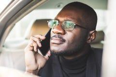 Homem de negócios bem sucedido novo que fala no telefone que senta-se no assento traseiro de um carro caro Negociações e negó imagem de stock