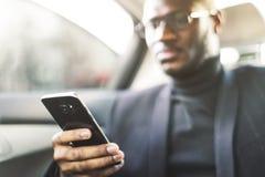 Homem de negócios bem sucedido novo que fala no telefone que senta-se no assento traseiro de um carro caro Negociações e negó fotografia de stock