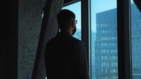 Homem de negócios bem sucedido novo que olha para fora a janela na baixa Edifício elevado do negócio Escritório no estilo do sótã vídeos de arquivo
