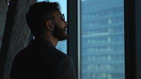 Homem de negócios bem sucedido novo que olha para fora a janela na baixa Edifício elevado do negócio Escritório no estilo do sótã filme