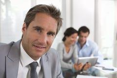 Homem de negócios bem sucedido que está com seu pessoal no fundo em Fotos de Stock Royalty Free