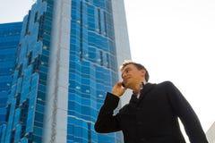Homem de negócios bem sucedido que fala no telefone móvel Fotografia de Stock Royalty Free