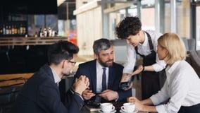 Homem de negócios bem sucedido que faz o pagamento em linha digital no café usando o smartphone video estoque