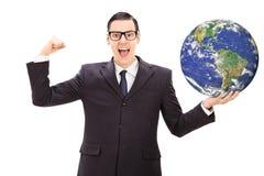 Homem de negócios bem sucedido que guarda o mundo Imagem de Stock