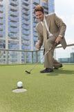 Homem de negócios bem sucedido que joga o golfe do telhado Fotografia de Stock Royalty Free